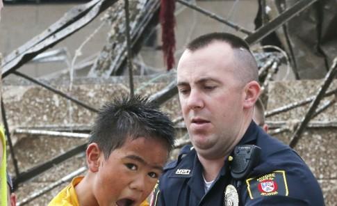 Este niño sobrevivió al derrumbe de su escuela. Abajo, una dama carga a otra estudiante.