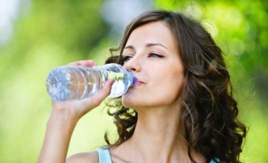 Mujer bebiendo agua tras ejercitarse