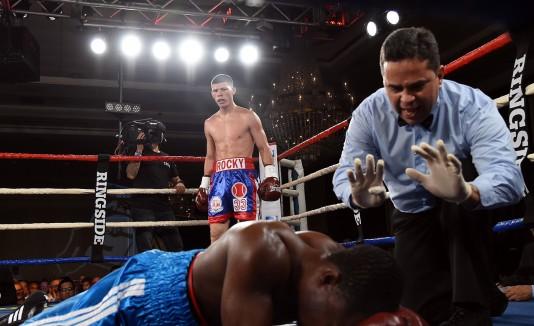 """El árbitro José Hiram Rivera hace el conteo reglamentario a Herbert Quartey (en la lona) tras el potente golpe recibido por Román """"Rocky""""  Martínez (observa de pie)."""