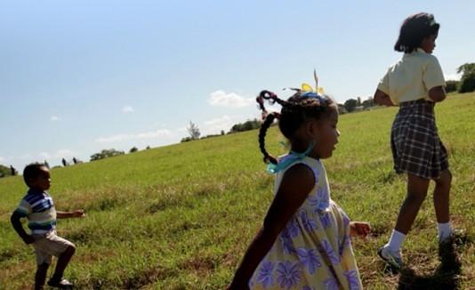 Niños de la comunidad Villas del Sol, en Toa Baja, corren por el terreno que el municipio les designó en el 2010.