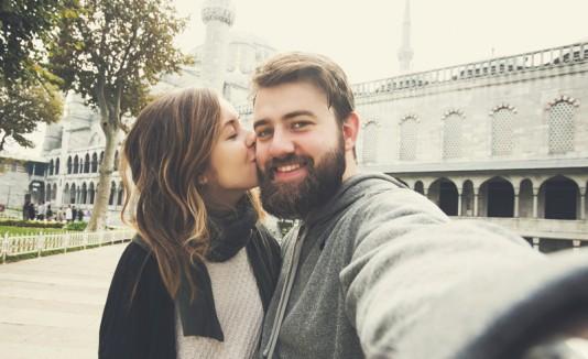Mujer besando a un hombre con barba.