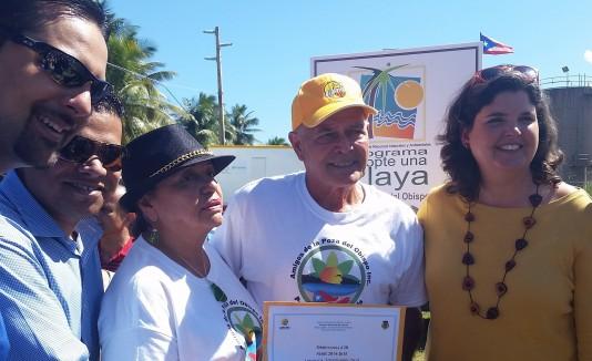 La secretaria del DRNA, Carmen Guerrero (der.), hace entrega del documento oficial  a los Amigos de la Poza del Obispo en Arecibo.