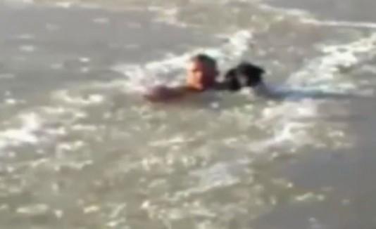 Hombre nadando con su perro en río congelado.