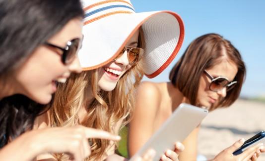 Mujeres alegres en una playa, planificando un viaje