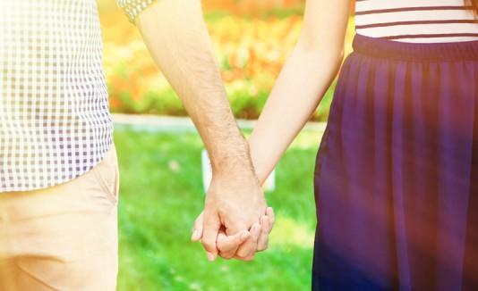 Pareja demostrando amor agarrados por sus manos