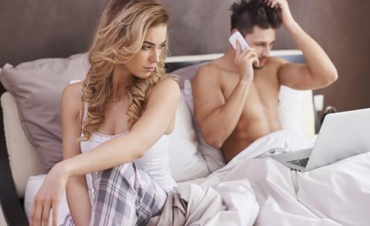 Pareja en la cama, y el hombre tiene celulary laptop en mano