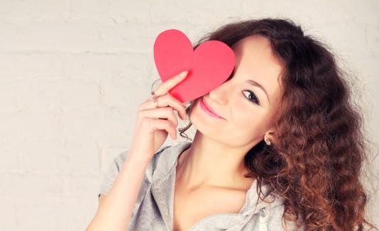 Mujer con un corazón en la cara en señal de enamoramiento