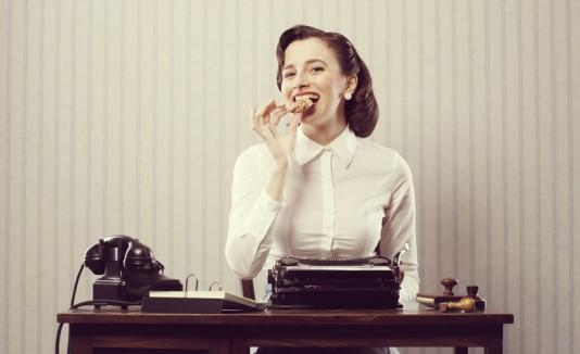 Mujer comiendo en un escritorio