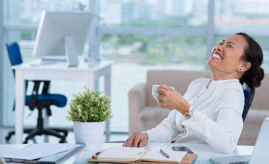 Mujer feliz en el trabajo con café