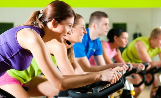 Personas corriendo biclicleta o haciendo spinning en un gimnasio