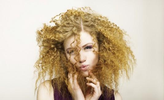 Mujer con cabello rizo, rubio y seco.
