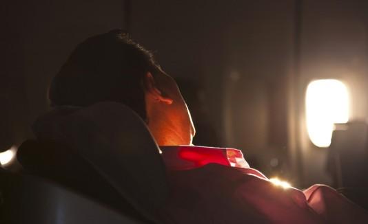 Hombre durmiendo en avión.