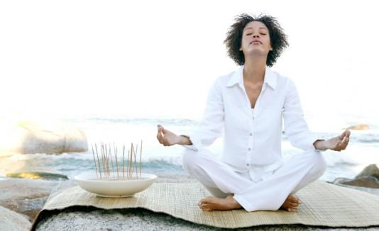Mujer respitando mientras hace yoga.