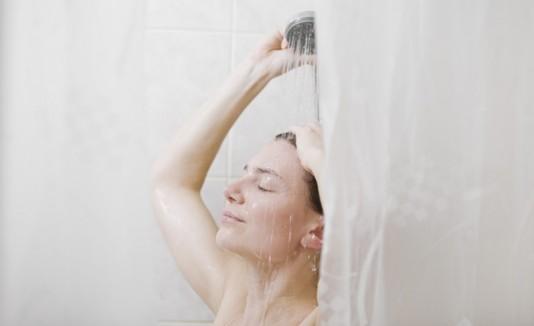 Mujer tomando una ducha en el baño.
