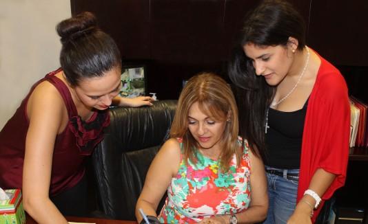 Melva Arbelo firma el acuerdo junto a estudiantes de la UPRA.