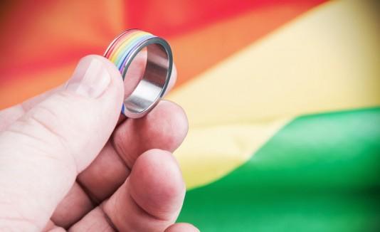 Anillo y bandera gay, representando matrimonio gay.