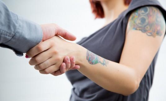 Mujer con tatuajes en entrevista de trabajo.