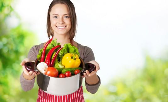 Mujer con frutas y vegetales en una olla