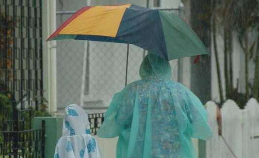 Señora u niña usan capas para taparse de la lluvia