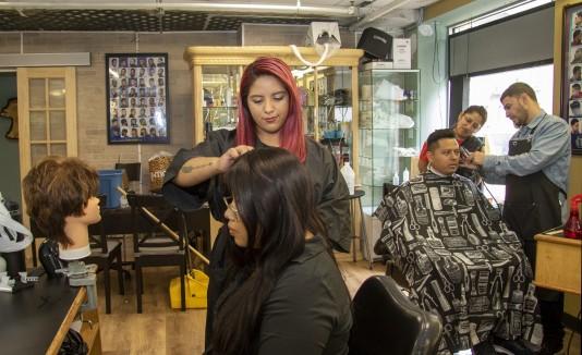 Unos estudiantes de la Escuela de Belleza Parisien cortan el pelo a unos clientes