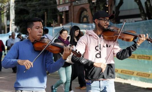 los músicos venezolanos Ángel García (violín), y Erick Sánchez (viola), mientras actúan en las calles de Bogotá (Colombia)