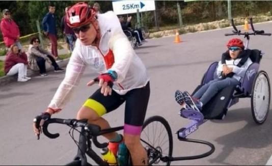 Óscar Caro hala la bicicleta de su hijo Luis David durante la edición 2018 de la triatlón de Paipa, Boyacá.  Foto: Cortesía Team Caro Wagner