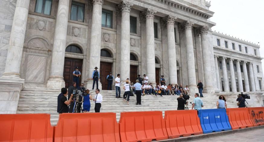 Ciudadanos y manifestantes se sentaron en las escalinatas del Capitolio luego de que se les impidiera en acceso a las gradas de la Cámara de Representantes, donde se discute el proyecto que elimina la Comisión de Auditoria Integral del Crédito Público.