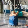 Mujer durmiendo en un aeropuerto.