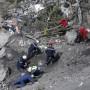 Varios trabajadores buscan entre los escombros del accidente aéreo.
