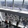 Varias personas observan las vistas desde el nuevo observatorio del edificio One World Trade Center.