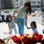 Una madre con sus hijos dejan unas flores en memoria de las víctimas de la masacre de Niza, delante de la embajada de Francia en Moscú, Rusia.